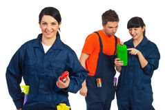 Cheerful cleaning worker woman and her team. Cheerful cleaning worker woman in front of camera and her team having conversation in background stock photo