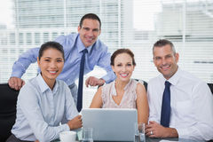 Cheerful colleagues around laptop posing Stock Photos