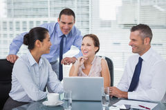 Cheerful colleagues around laptop working together royalty free stock photos