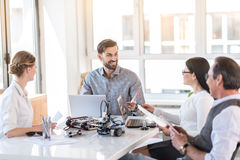 Cheerful colleagues communicating in office Stock Photo