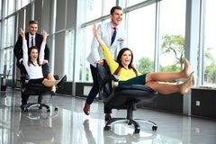 Cheerful colleagues having fun in office chairs. Cheerful colleagues having fun in office chairs stock image