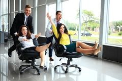 Cheerful colleagues having fun in office chairs. stock images