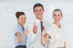 Cheerful colleagues posing with thumbs up Royalty Free Stock Image