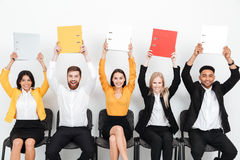 Cheerful colleagues sitting in office holding folders. Picture of a group of cheerful colleagues sitting in office holding folders. Looking at camera Stock Images