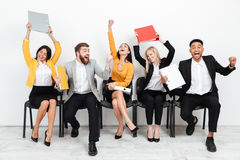 Cheerful colleagues sitting in office holding folders. Royalty Free Stock Photos