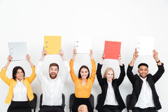 Cheerful colleagues sitting in office holding folders. Stock Photo