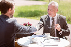 Cheerful colleagues sitting at the table. Find right decision. Pleasant cheerful smiling colleagues sitting at the table and shaking hands while expressing royalty free stock photos