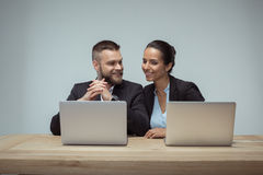 Cheerful colleagues using laptops on workplace in office. Portrait of cheerful colleagues using laptops on workplace in office royalty free stock image