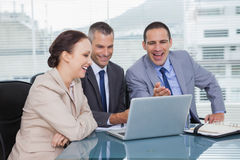 Cheerful colleagues working together on their laptop Royalty Free Stock Images