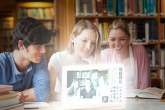 Cheerful college friends watching photos on digital interface Stock Photos