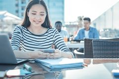 Cheerful college girl browsing smartphone while studying. Getting updated. Relaxed young lady reading news on her smartphone and smiling while working on her Stock Photos