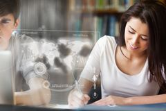 Cheerful college student analysing map on digital interface. In university library Royalty Free Stock Photos