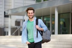 Cheerful college student standing outside with back