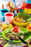 Cheerful and colorful food for children. Fun food for kids with salad, baked tomatoes stuffed with egg and berry drink on a laid table decorated with toys and Stock Photo