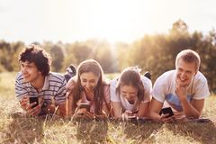 Cheerful companions smile while tell each other anecdotes, use modern smart phones, have picninc outdoor in countryside, enjoy sun. Ny day. Teenagers, technology Stock Photography