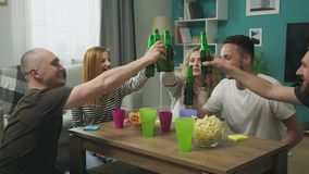 Cheerful company of friends drink beer in a cozy living room stock footage