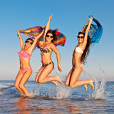 Cheerful company of girls jumping in the sea royalty free stock images