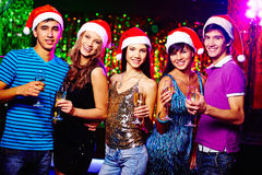 Cheerful company. Young glamorous friends in Santa caps looking at camera while toasting with champagne stock photos