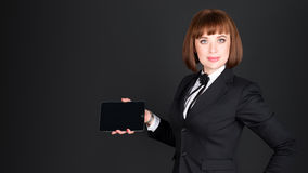 Cheerful confident business woman on black background showing blank tablet computer screen in dark office with copyspace Royalty Free Stock Photography