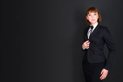 Cheerful confident business woman standing in dark office room and looking at camera. Charming businesswoman on black Stock Image