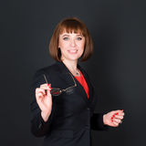 Cheerful confident business woman standing in dark office room and looking at camera holding glasses. Charming Royalty Free Stock Photo