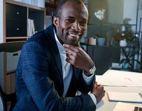 Cheerful confident manager is expressing gladness. Strong and successful. Portrait of positive delightful young african businessman is sitting at table while stock photography