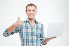 Cheerful confident young man holding laptop and showing thumbs up Royalty Free Stock Image
