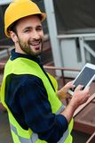 Cheerful construct worker in safety vest and helmet using digital tablet. With blank screen stock photography