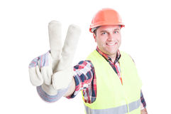 Cheerful constructor doing victory or peace sign Royalty Free Stock Image