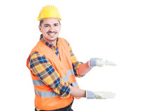 Cheerful constructor showing something small with his hands Royalty Free Stock Image
