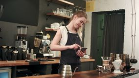 Cheerful and content female barista using mobile phone and texting at coffee shop stock video footage