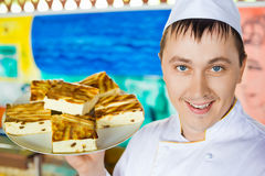 Cheerful cook holding cheese baked pudding on dish Stock Photo