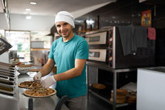 Cheerful cook kitchen ingredients in pizza places. Side view. Stock Photo