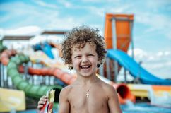 Joyful cheerful curly-haired boy stands near the pool and eats before riding on the gorges in the water park on a summer vacation