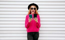 Cheerful cool girl holding two phone and looking at them on white wall. Background royalty free stock photo