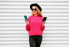 Cheerful cool girl holding two smartphone and looking at them in city on white wall. Background royalty free stock images