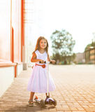 Cheerful cool little joyful girl in dress on the scooter. In the city Royalty Free Stock Photos