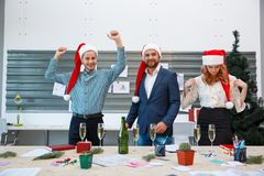 Young happy friends celebrating New Year on a blurred background. Christmas party with Santa hats concept. Cheerful corporate colleagues enjoying office New Royalty Free Stock Images