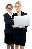 Cheerful corporate ladies using laptop Stock Photos