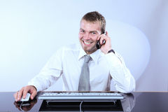 Cheerful Corporate Man On The Phone. Cheerful Corporate Man Talking On The Phone And Working On Computer Stock Photos