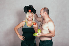Cheerful corpulent couple with fruit and vegetable royalty free stock images