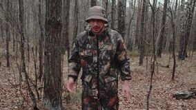 Cheerful correspondent reporter tells something to camera in forest. Hunter ranger dressed in a camouflage suit. Man