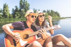 Cheerful couple with acoustic guitar sitting on pier and singing. Lake and trees in the background. Young couple in love singing their favorite song and playing stock images