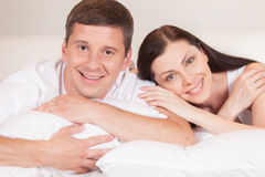 Cheerful couple awaking and lying happy. Royalty Free Stock Photo