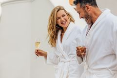 Cheerful couple in bathrobe. Talking and laughing. Man and women in bathrobes holding a glass of wine and smiling stock image