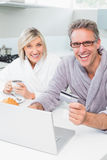 Cheerful couple in bathrobes using laptop in kitchen Royalty Free Stock Photo
