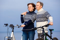 Cheerful couple biking on a sand beach Royalty Free Stock Photo