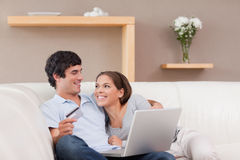 Cheerful couple booking holiday online Stock Photos