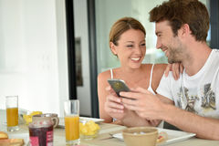 Cheerful couple at breakfast time Royalty Free Stock Image