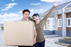 Cheerful couple carrying box at new house Stock Photography